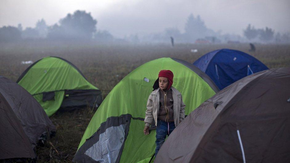 Chlapec stojí u stanů, které si postavili uprchlíci v noci u srbsko-chorvatských hranic.