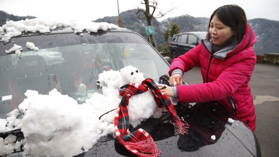 Žena v Jižní Korey uklízí auto po sněhové bouři.