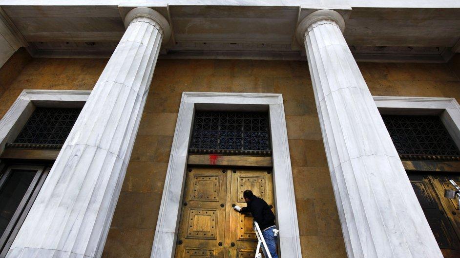 Muž odstraňuje barvu, kterou nechali demonstranti na dveřích řecké centrální banky v Aténách.