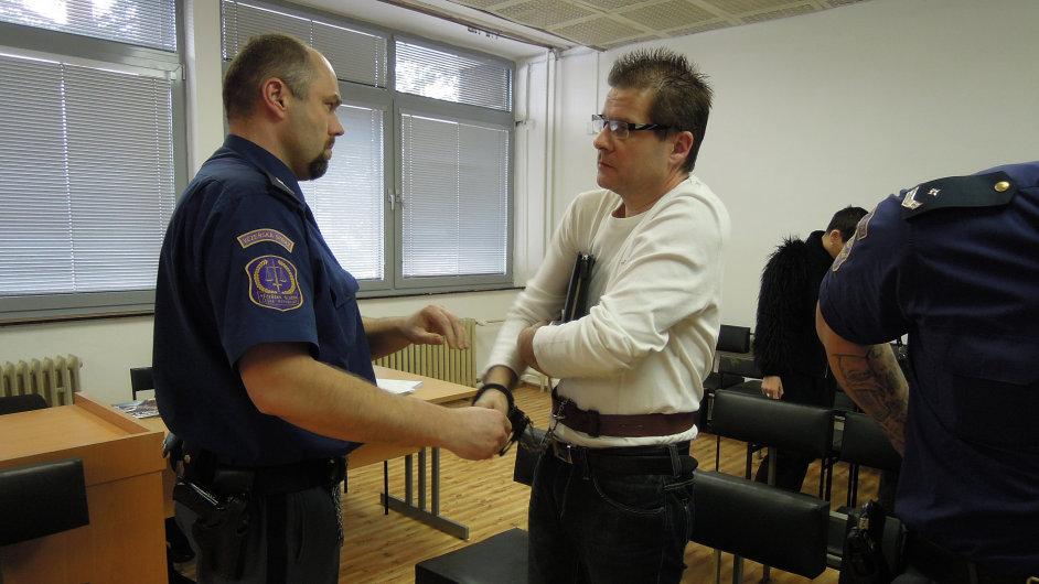 Justiční stráž přivedla Kušnierze do soudní síně v poutech.