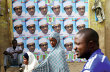 People walk in front of election posters of presidential candidate Muhammadu Buhari gestures in Kano March 27        TPX IMAGES OF THE DAY      - RTR4V6B5