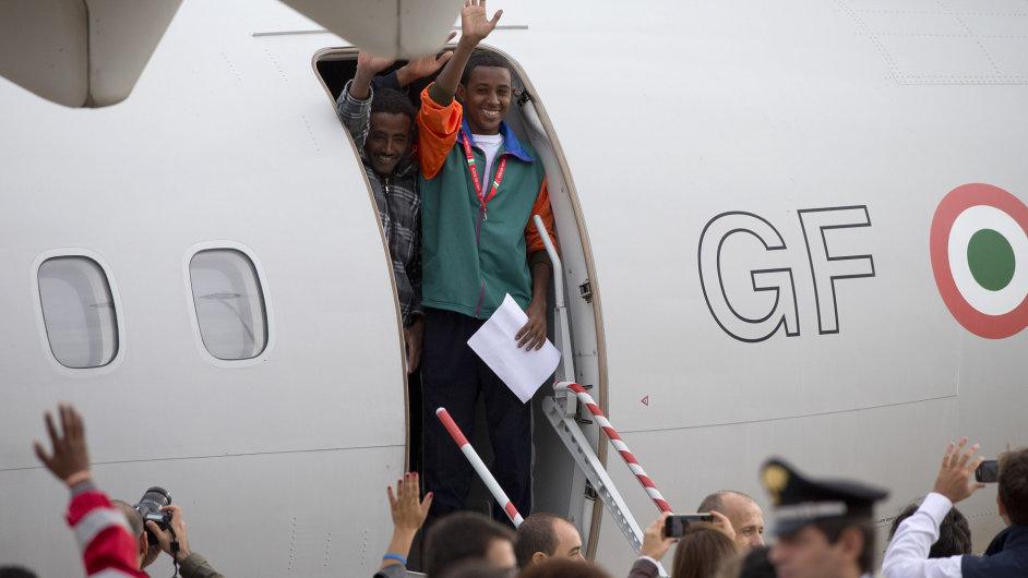 Eritrejští uprchlíci mávají z paluby letadla, které je odveze do Švédska.