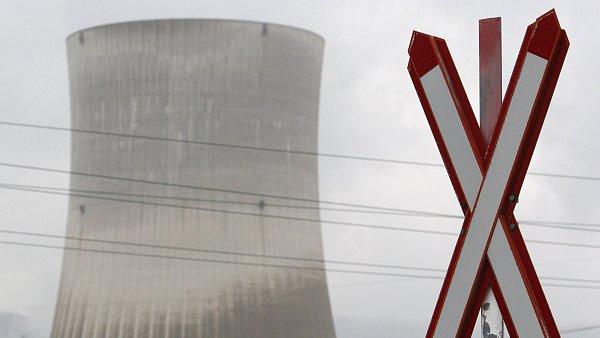 Ilustrační foto - Výstražné znamení na železničním přejezdu v popředí chladící věže jaderné elektrárny ve švýcarském Goesgenu.