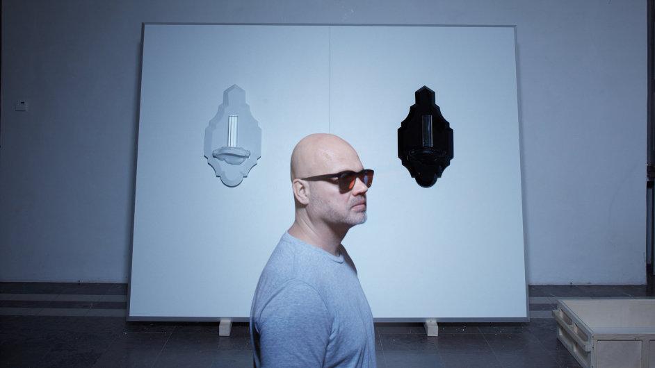 Designér a výtvarník Rony Plesl, v pozadí jeho dílo Bílý a černý oltář.