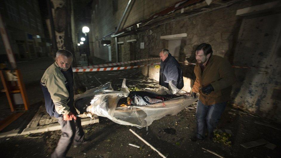 Obyvatelé Doněcku odklízejí tělo zabitého zaměstnance Červeného kříže