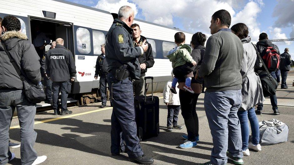 Uprchlíci, hlavně ze Sýrie, mluví s dánským policistou na nádraží v Rodby - Ilustrační foto.