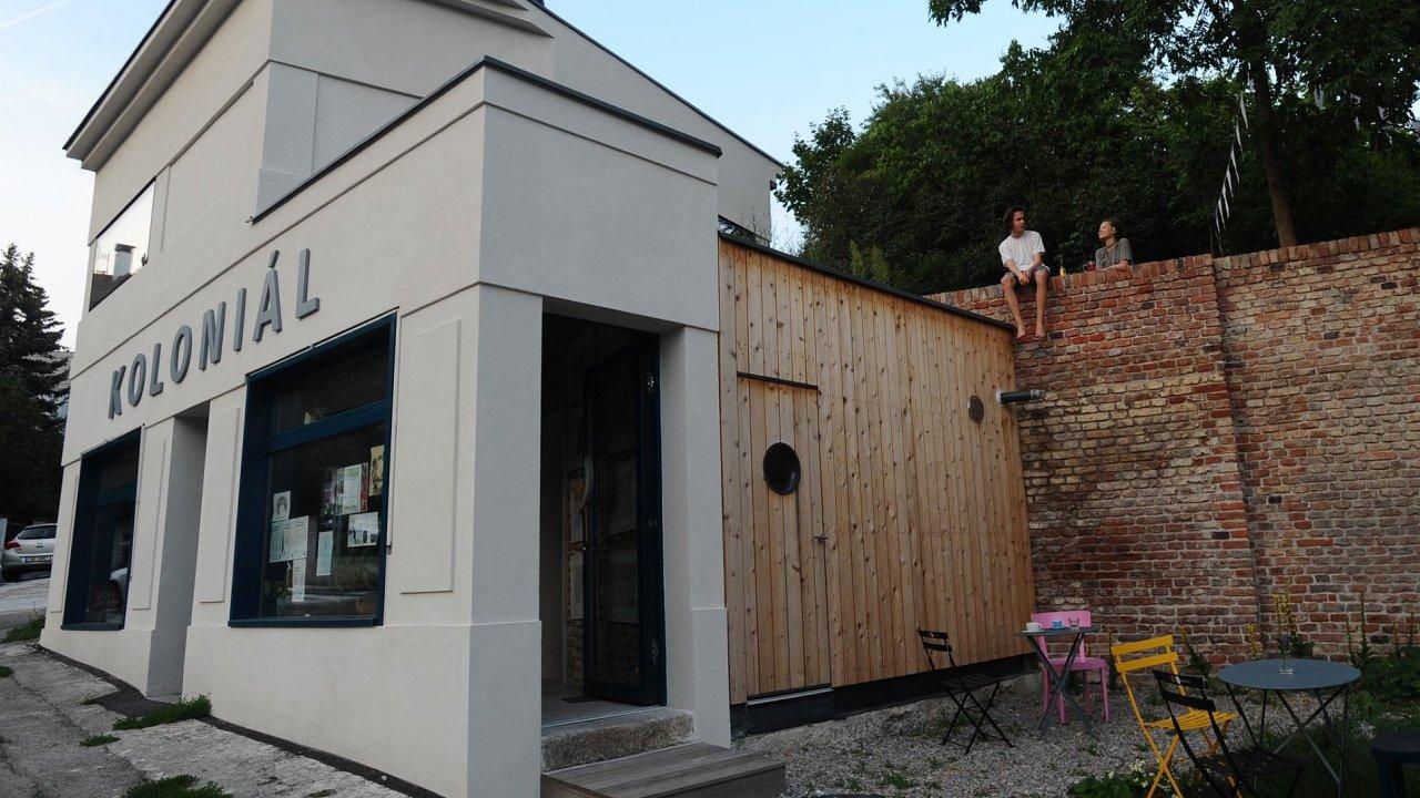 Budova bývalého koloniálu byla vhodně rekonstruována adostavěna podle návrhu Lennox architektů, bezprostřední okolí nazměny veformě stíněných dřevěných palub čeká.