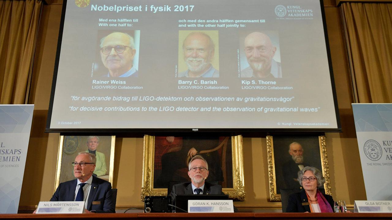 Laureáty Nobelovy ceny za fyziku jsou v letošním roce tři Američané (nahoře na plátně).
