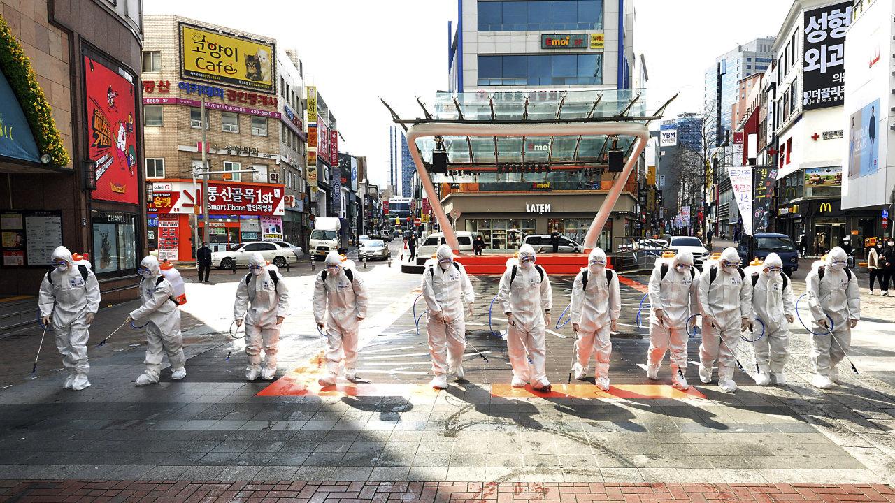Vojáci v Jižní Koreji dezinfikují v ochranných oblecích ulice. Snaží se tak zabránit šíření koronaviru.