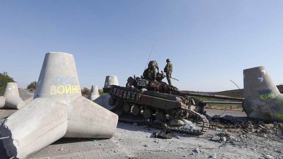 Ukrajinští vojáci si prohlížejí poškozený tank na předměstí Mariupolu