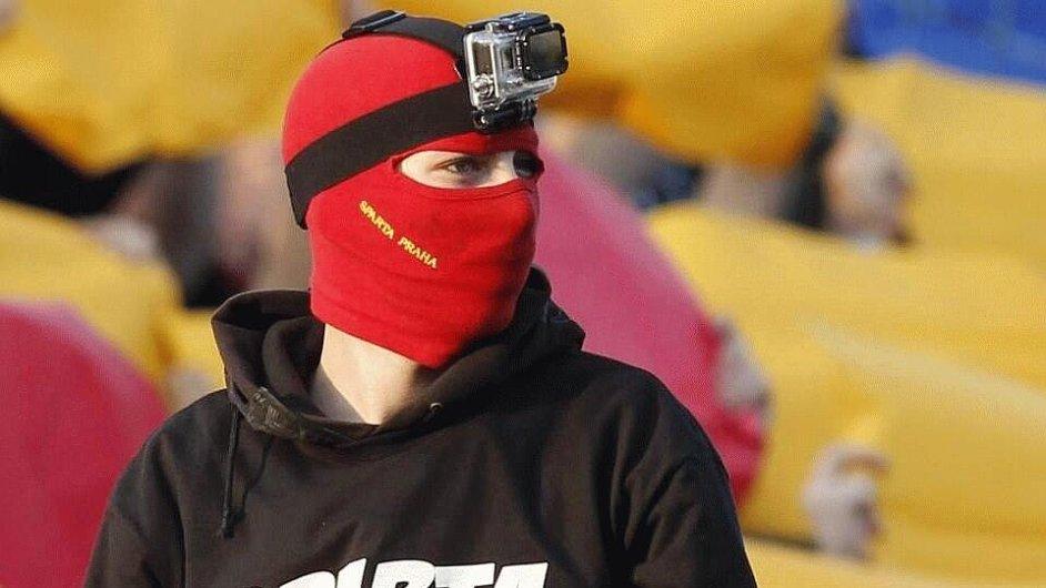Maskovaný chuligán si na fotbal potřebuje posvítit.