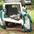 Zdravotn�ci odn�ej� t�lo jedn� z ob�t� viru ebola v Sie�e Leone.