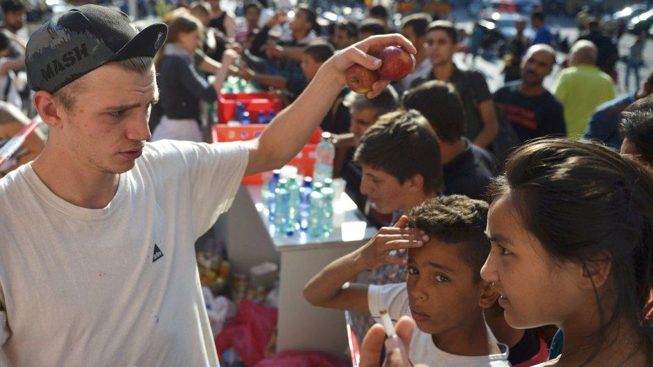 Mladík rozdává uprchlíkům ovoce na hlavním nádraží v Mnichově.