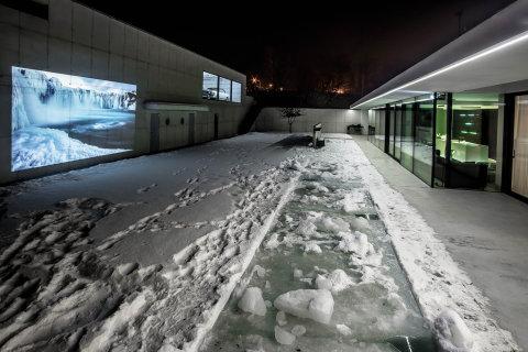 Betonová plocha budovy oddělující pozemek od rušné ulice za tmy poslouží i jako projekční plocha domácího kina.