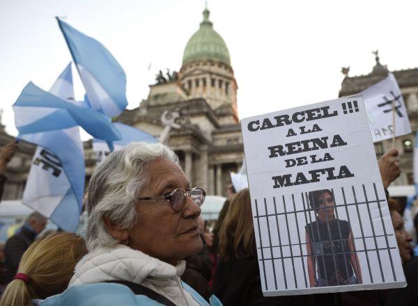 """Demonstrantka držící transparent se španělským nápisem: """"Vězení! Mafiánská královna""""."""