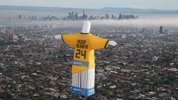 """Sázková kancelář Sportbet nechala v souvislosti se šampionátem ve fotbale nad městem Melbourne umístit reklamního Krista, který má obyvatele přesvědčit, že """"království výher"""" přichází."""