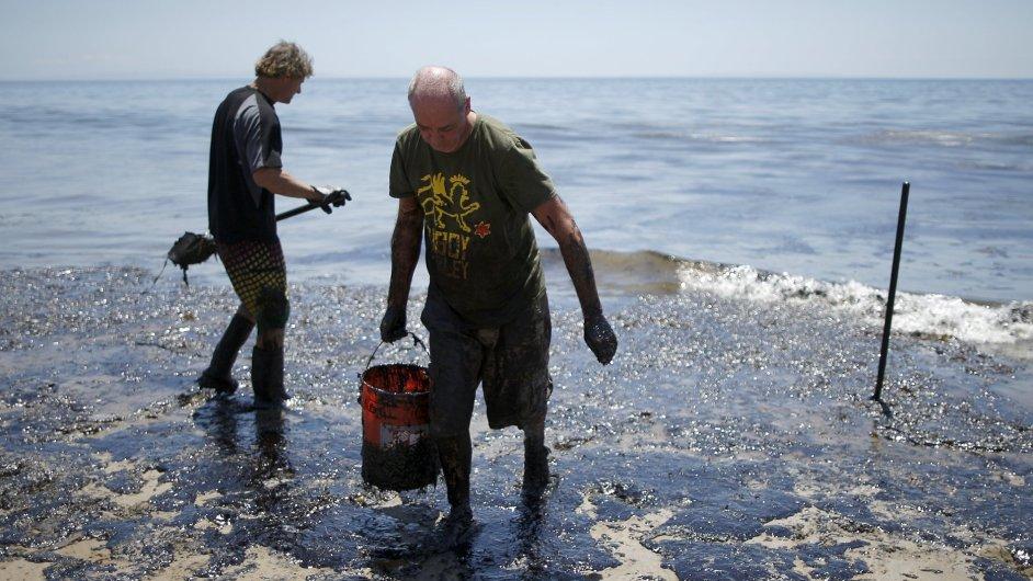 Dobrovolníci pomáhají s odklízením ropné skvrny.