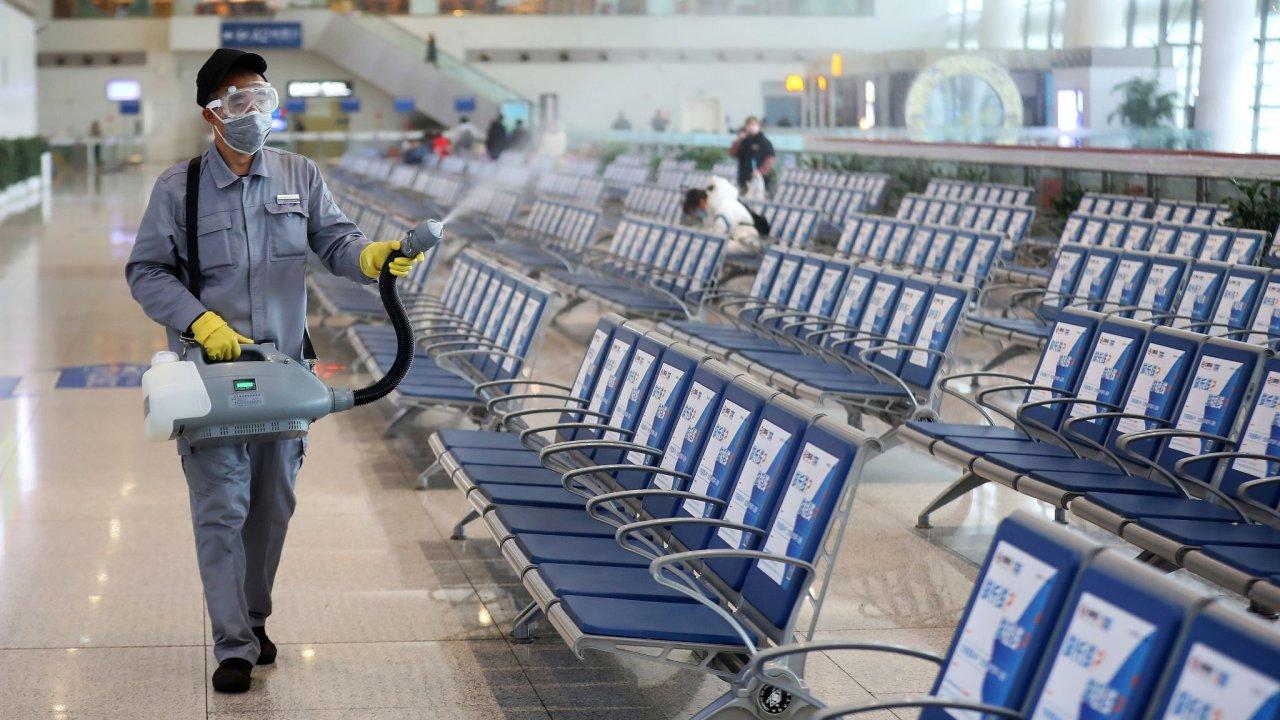 Pracovník v ochranné masce dezinfikuje halu vlakového nádraží v Nankingu kvůli šíření nového koronaviru.