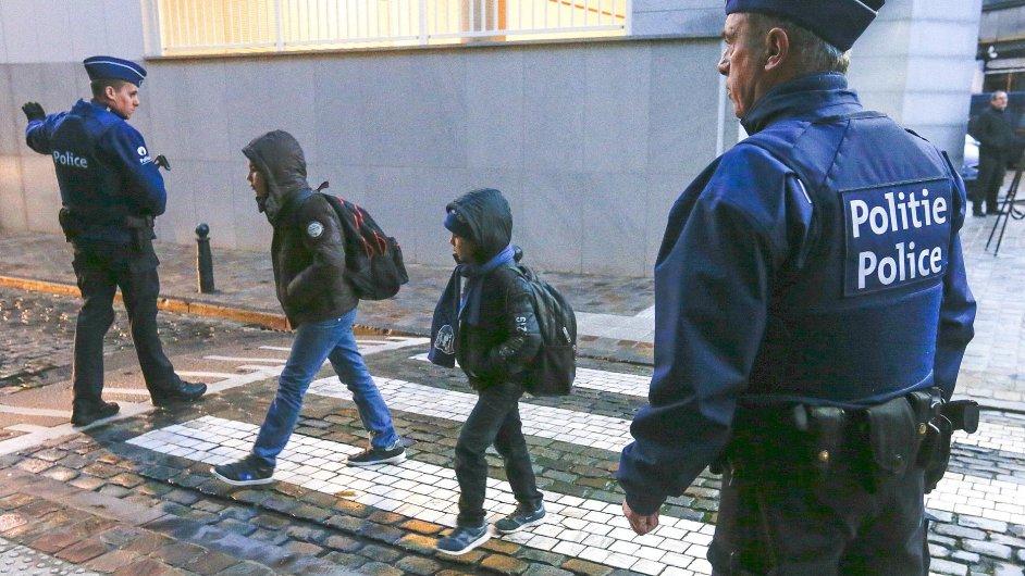 Policista hlídkuje před školou.