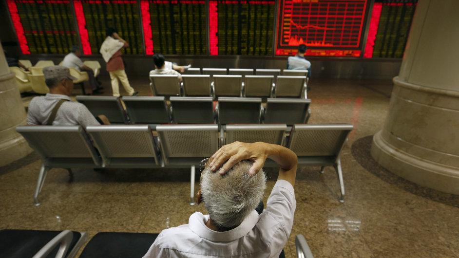Čínský investor sleduje pondělní propad cen akcií v centrále makléřské společnosti v Pekingu.