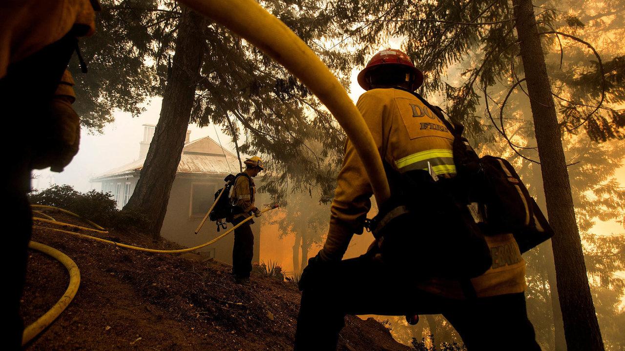 Západ Spojených států kvůli požárům zahalila oranžová záře aštiplavý kouř. Nasnímku zkonce minulého týdne hasiči bojují splameny poblíž kalifornského Los Angeles.