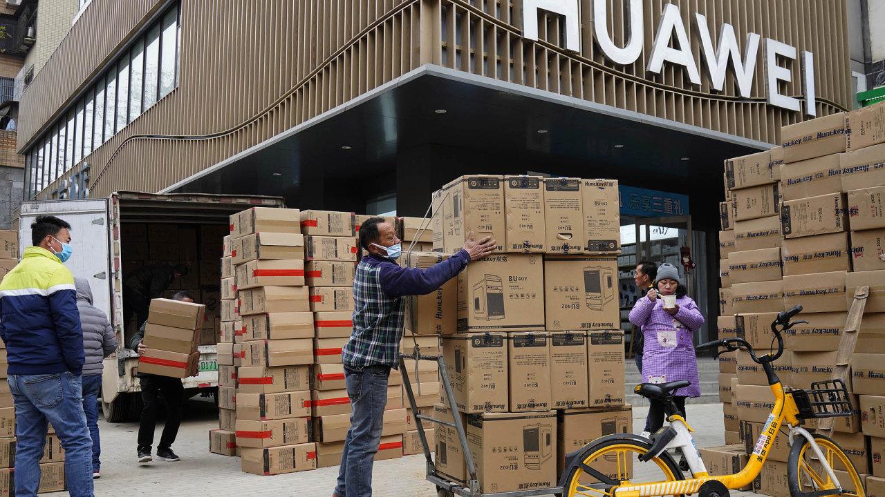 Dělníci veWu-chanu přejímají zásilku počítačů. Ty patří keklíčovým položkám čínského vývozu. Zvláště vdobě, kdy spousta lidí vesvětě pracuje zdomova.