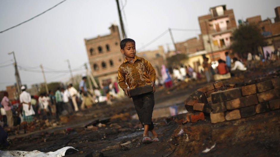 Indický chlapec prochází po požáru slumem v Novém Dillí