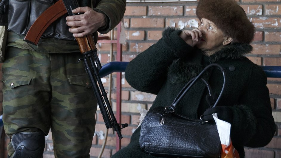 Žena v Doněcku vzhlíží k ozbrojenci, který patří k místním proruským separatisům.