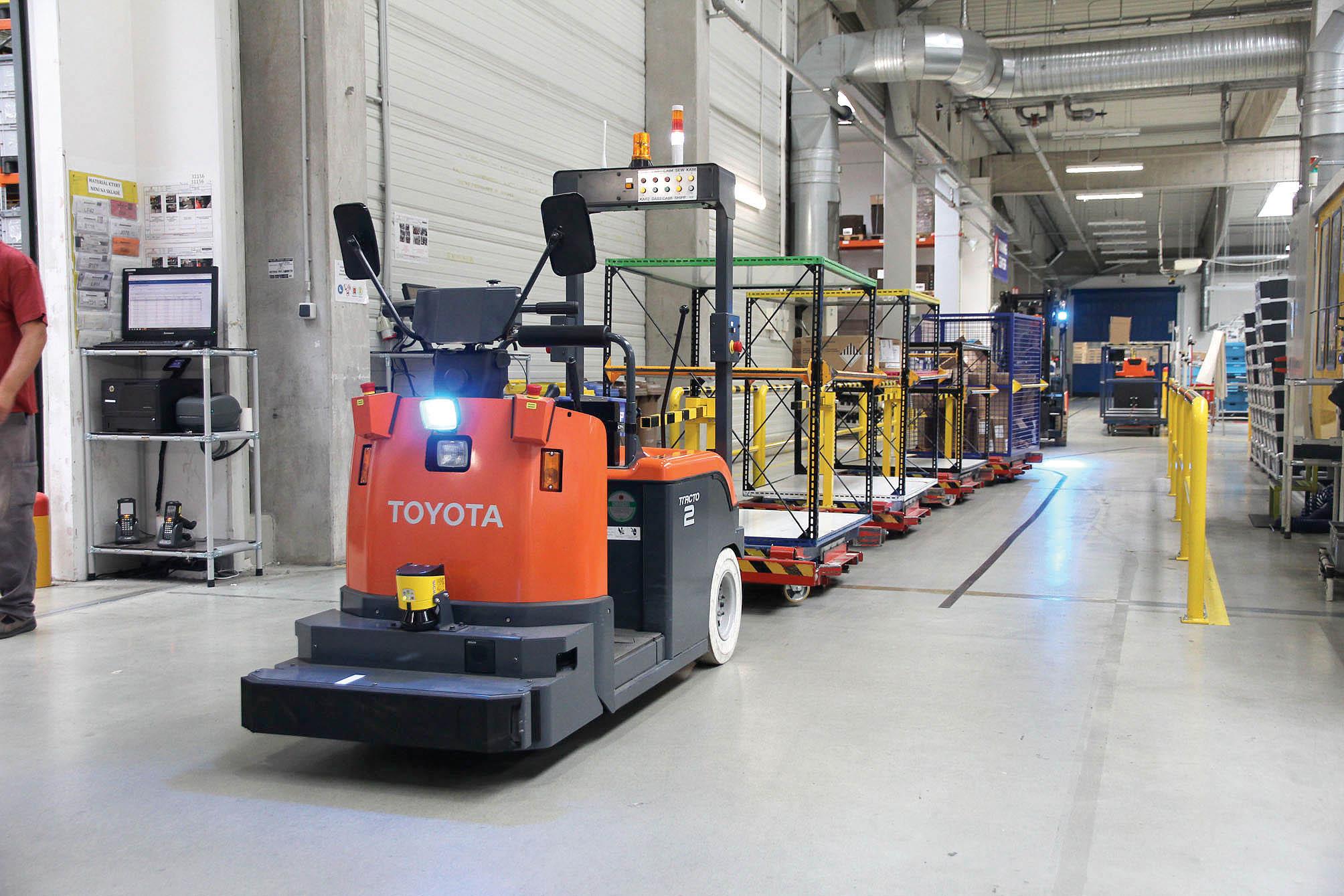 Tovární halou projíždí automatický tahač Toyota Tracto svláčkem.