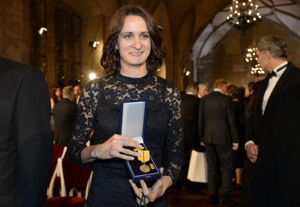Rychlobruslařka Martina Sáblíková ukazuje medaili za zásluhy, kterou převzala od prezidenta Miloše Zemana při slavnostním ceremoniálu udílení státních vyznamenání