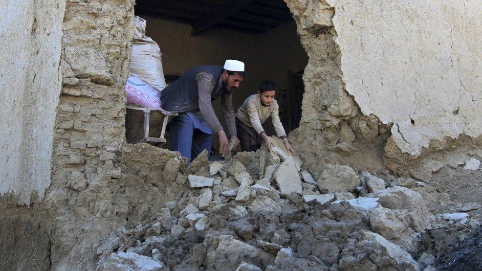 Otec se synem uklízí sutiny svého domu v provincii Nangarhar poblíž Pákistánu poté, co oblast zasáhlo pondělní zemětřesení.