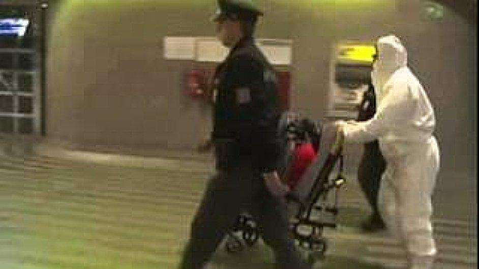 Zdravotník převáží ghanského studenta na Hlavním nádraží v Praze do karantény.