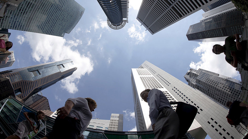 People walk past office buildings at the central business district in Singapore April 14