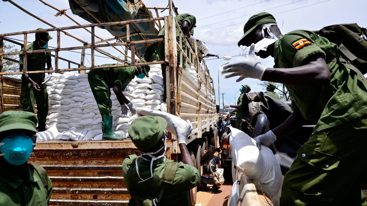 Příslušníci domobrany distribuují zdarma jídlo obyvatelům hlavního ugandského města Kampala, na něž dolehla opatření přijatá proti šíření koronaviru.