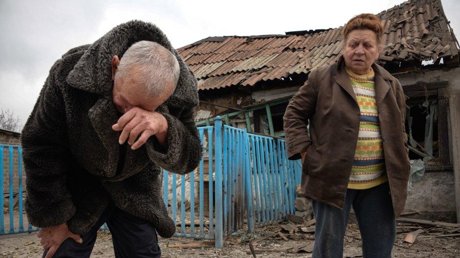 Valentina Fedorjak stojí s manželem před zničeným domem v Doněcku. Boje tam neustávají.