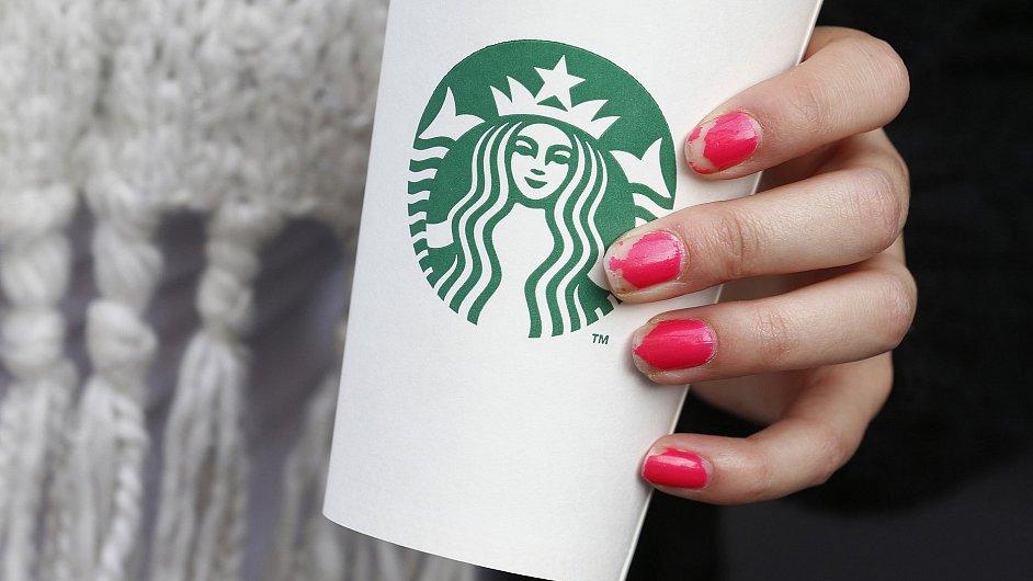Logo Starbucksu na jeho kelímku od kávy.