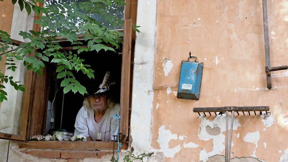 Ivan Martin Jirous v okně svého chátrajícího statku v Prostředním Vydří u Dačic