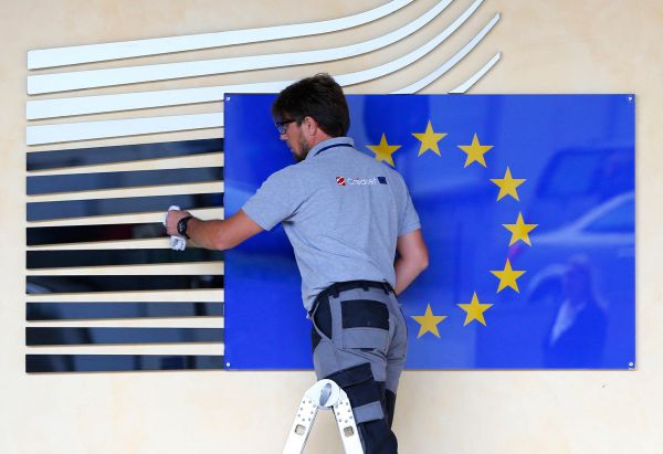 A worker adjusts and cleans the logo of the European Commission at the entrance of the Berlaymont building