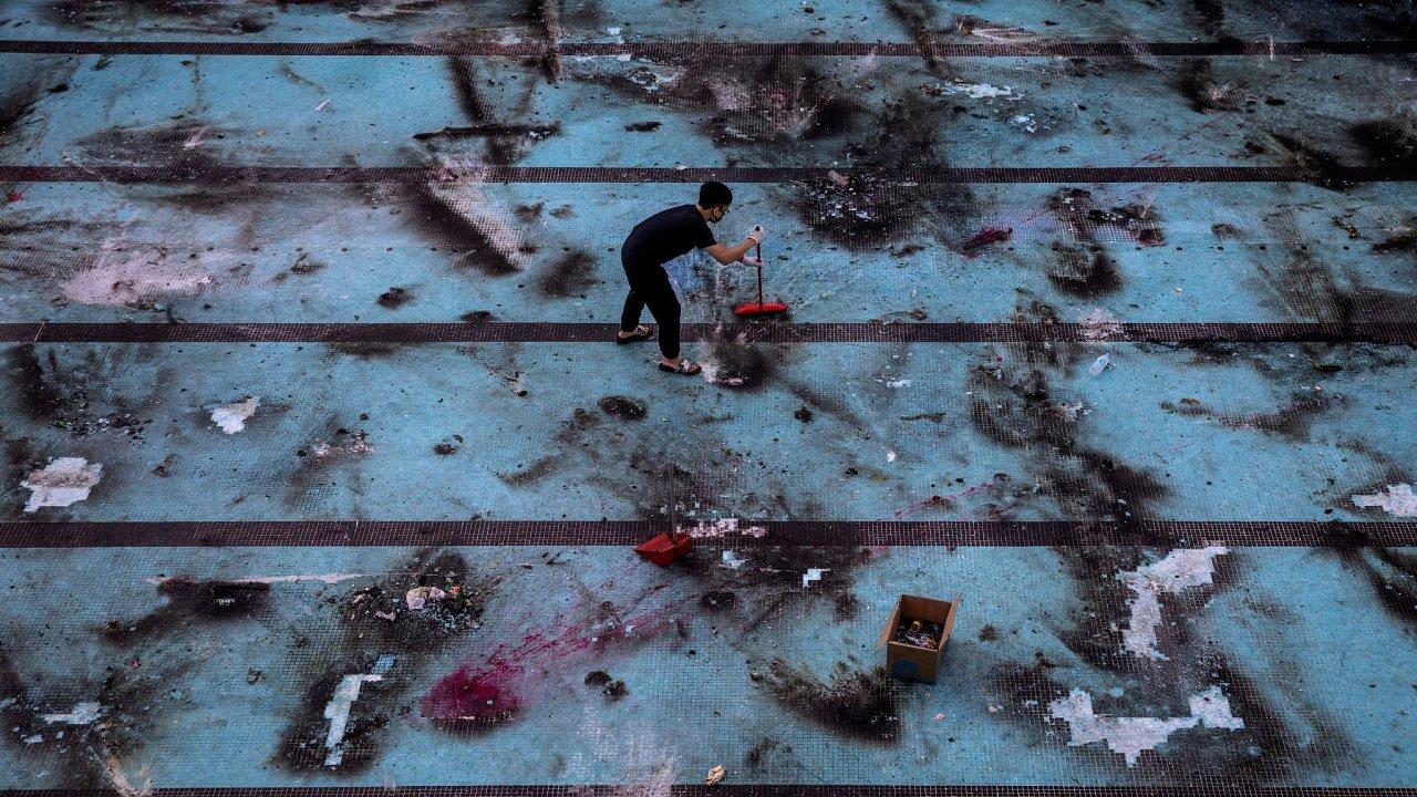 Pracovník odklízí následky střetů mezi demostranty a policií na hongkongské Polytechnické univerzitě.
