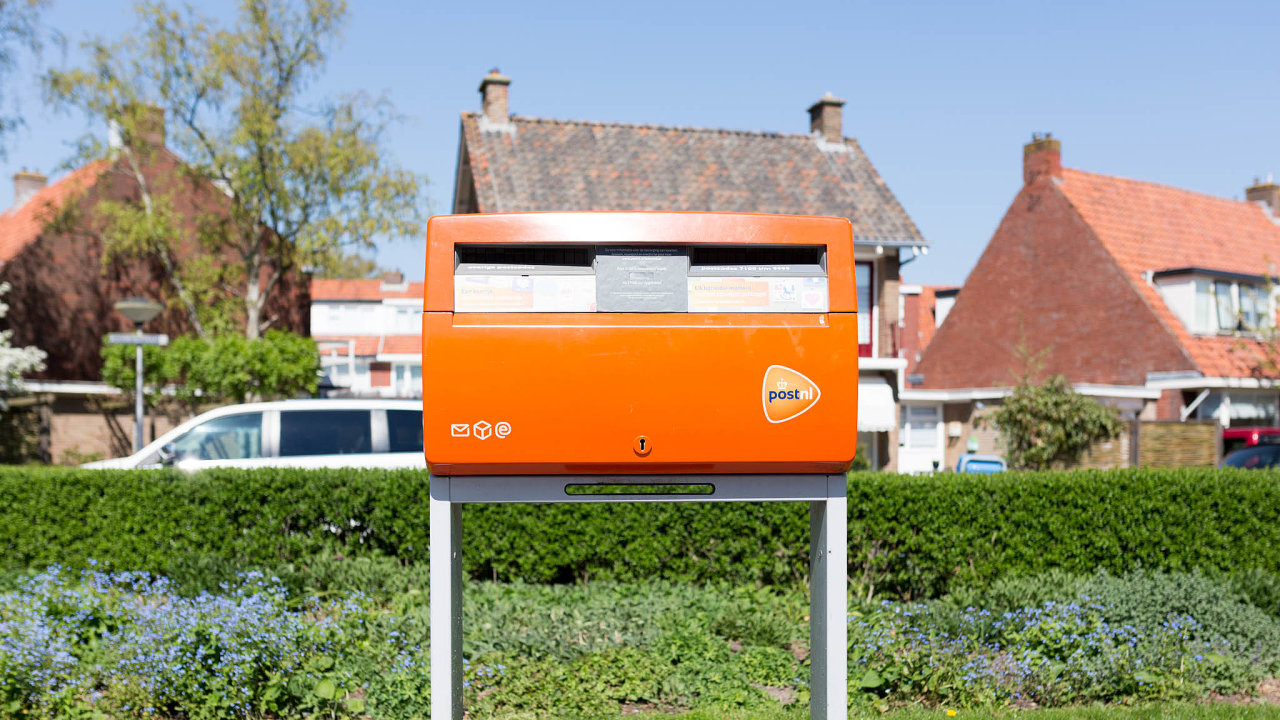 Leeuwarden, The Netherlands - April 2019. Orange mailbox by logistics company PostNL in a suburban area