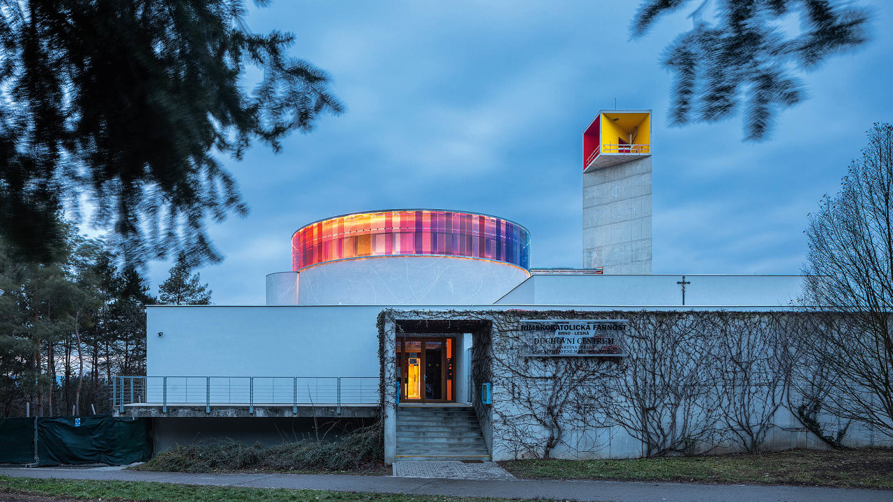 Betonovému kosteludominují věž apás barevných oken.