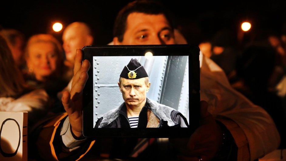 Protestující obyvatel Kypru drží v ruce tablet s fotkou ruského prezidenta Vladimíra Putina.