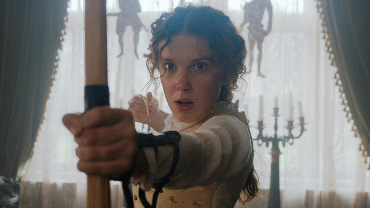 Enola Holmesová (Millie Bobby Brownová) se nechová jako mladé dámy ve viktoriánské Anglii. Matka ji naučila i střílet z luku.