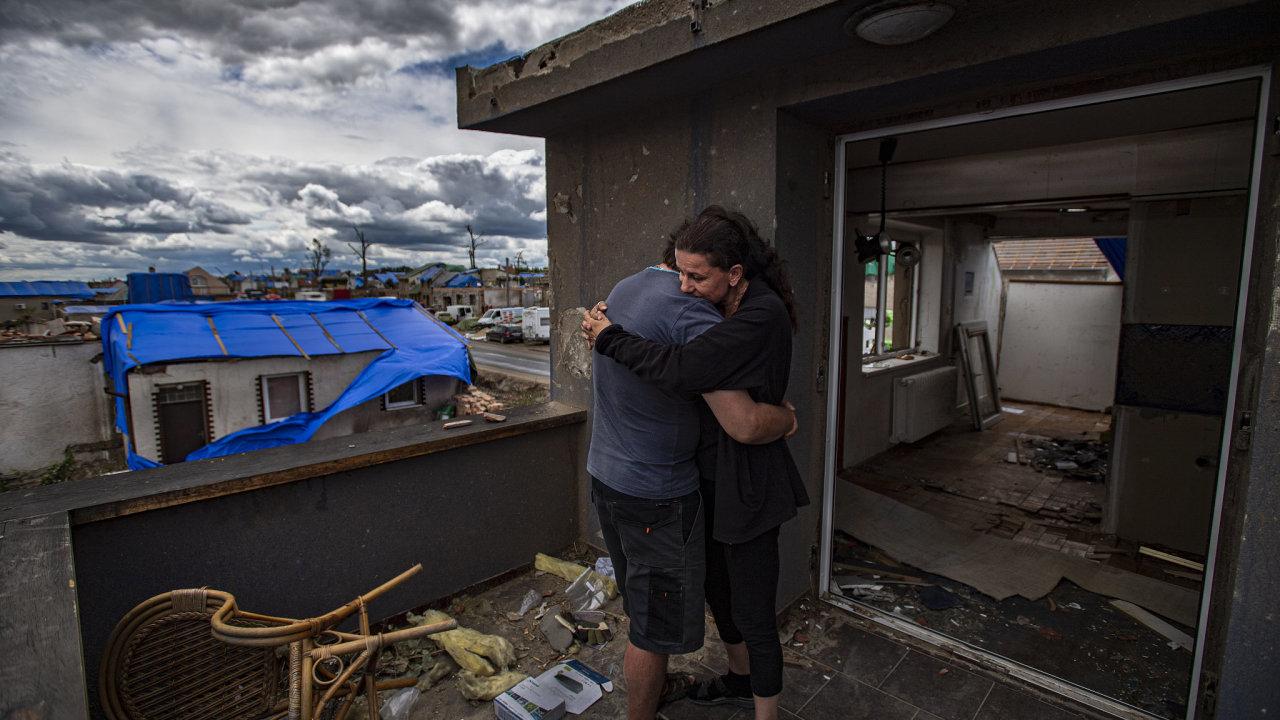 Pavel a Michaela v objetí před vstupními dveřmi jejich poškozeného domu, který v následujících dnech čeká kompletní demolice, Mikulčice na Hodonínsku