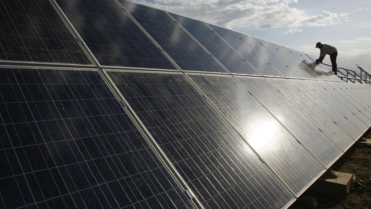 Dělník instaluje solární panely na elektrárně ve městě Hami v čínské provincii Sin-ťiang na archivním snímku z roku 2011.
