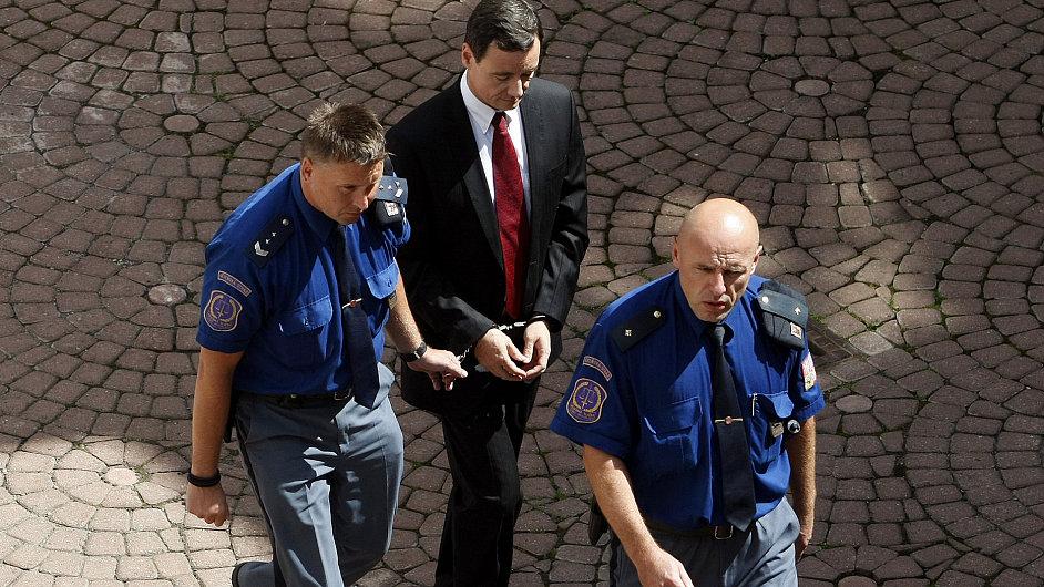 Policisté přivádějí Davida Ratha k soudu.