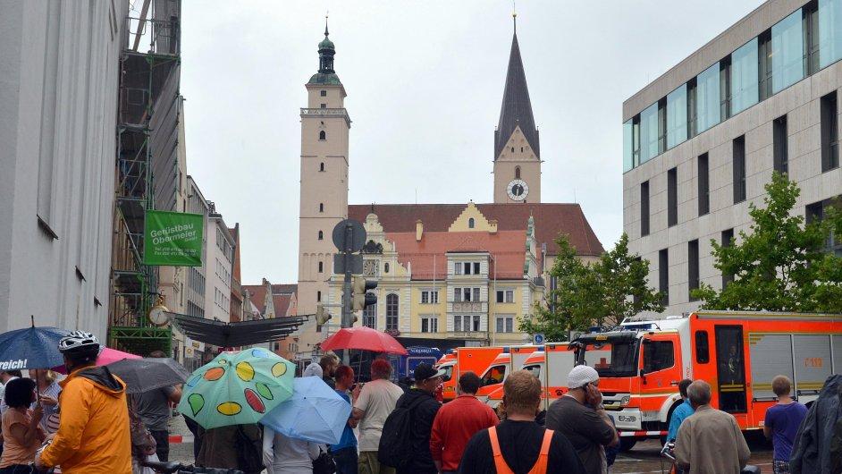 Kolemjdoucí pozorují radnici v Ingolstadtu, kde ozbrojený muž drží dvě ženy