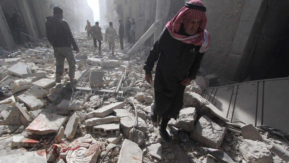 Muž překračuje trosky domů po sobotních náletech v syrském městě Aleppo.