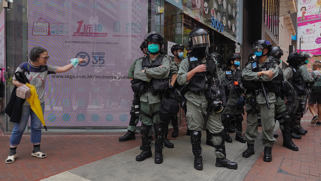 Hong Kong riot police standing guard as a women trying to cross the street in the Central district