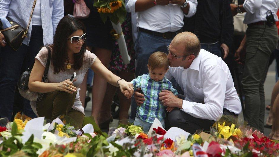 Muž s rodinou pokládá květiny k památníku dvou obětí střelby v centru Sydney